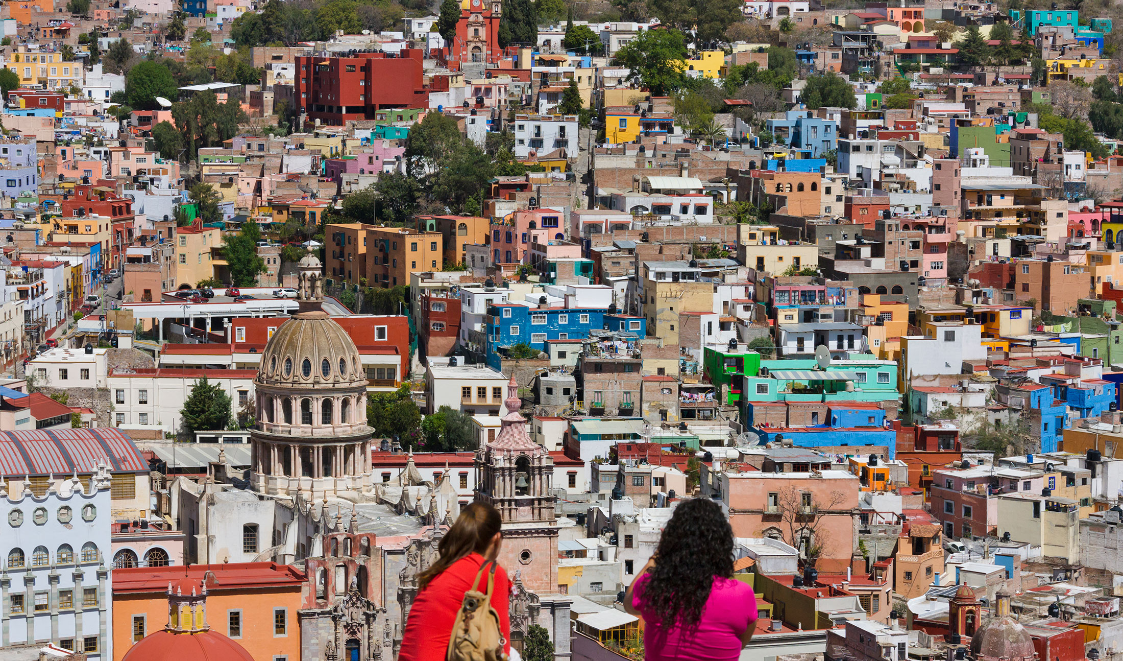 Tourists look out across the colourful houses of Guanajuato